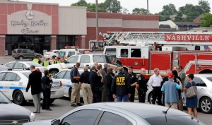 Officials work outside a movie theater complex following a shooting Wednesday, Aug. 5, 2015, in Antioch, Tenn. A man armed with a hatchet and gun unleashed a volley of pepper spray at audience members inside a movie theater, exchanging fire with a responding officer before being shot dead by a SWAT team as he tried to escape through the theater's rear door, police said. (AP Photo/Mark Humphrey)